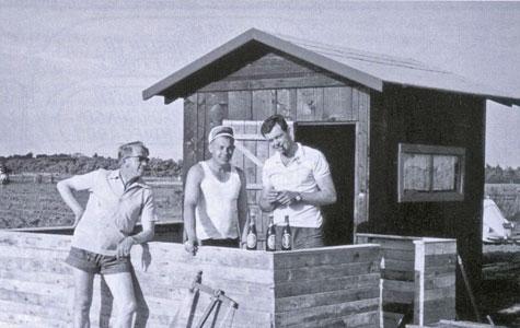 Der opstod ofte gode venskaber og fællesskaber mellem naboerne mens man byggede huse. Man hjalp hinanden og fulgte med i hvordan det for naboens byggeri. Og selv om arbejdet til tider var hårdt, var der også plads til hyggelige pauser. Her er det Kaj, der i 1964 sammen med sine to hjælpere fejrer at terrassen til det lille fritidsskur er blevet færdigt.