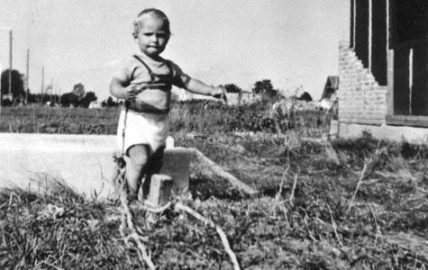 I den første tid var der hverken vuggestuer eller børnehaver til mange nye børn i Greve. Samtidig havde far og mor travlt med at bygge hus og det var farligt for et lille barn at gå frit omkring, da der var mange dybe huller det kunne falde. Her er et barn blevet tøjret til en pæl, så det ikke falder i et hul.