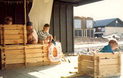 Hvis man var barn, var det alletiders at lege med brædder fra byggepladsene, som her hvor Sune og hans to fætre, Søren og Anders, leger i garagen på Margrethe Allé 24. De har bygget en båd af brædder. Foto fra 1969.