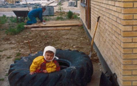 Hjemme hos værktøjsmager, Stig Knudsen. Hans søn Jens, sidder i en sandkasse. Stigs fætter lægger terassefliser. I baggrunden bygges Fritz Møllers bilforretning og Hedelyparken.