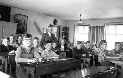 Elever og lærer Andersen i klasselokalet på Kildebrønde Skole. Sidste skoledag før elever og lærere blev flyttet til Greve-Kildebrønde Centralskole. Eleverne sidder ved topersoners skolepulte og skriver. I baggrunden ses kakkelovn og udstoppede dyr.