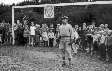 """Fodboldkampen mellem lærere og elever på Greve-Kildebrønde Centralskole i 1957. Pedellen (hr. Bech) står på mål. I hånden har han et fiskenet, på målet hænger et færdselsskilt: """"fuld stop""""."""