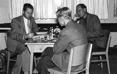 Eksamen i fysik på Greve-Kildebrønde Centralskole i slutningen af 1950'erne. Tv. hr. Knudsen. Eleven, der eksamineres, er Erling Hansen fra Greve, th. censor Kai Andreasen.