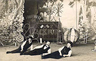 """De første fyrværkere, der var omvandrende gøglere og cirkus¬folk, brugte fyrværkeriet til at underholde med på linie med tryllekunst, akrobatik og fremvisning af """"sære ting"""". Her ses et postkort fra 1909 med tre fyrværkere liggende på en scene, i baggrunden ses forskellige typer fyrværkeri."""
