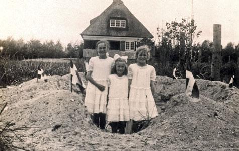 Søstrene Gerda, Agnete og Elisabeth Pind, har gravet et stort hul i sandet, og sat flag hele vejen rundt. Alle tre i hvide kjoler, købt i Magasin du Nord. I baggrunden ses Strandhuset, som var det sommerhus de boede i.