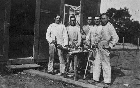 Nogle af soldaterne havde også håndværksmæssige opgaver, som her hvor 5 snedkere står foran barak i Grevelejren i sommeren 1917. De holder en sav med påskrift: Greve Lejren juni-juli 1917.