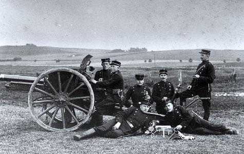 Soldaterne står med en feltkanon M/1902. Den var for sin tid en fremragende 75 mm hurtigskydende feltkanon, som - med forbedrede sigtemidler - var tjenestgørende i hæren lige til 1940.