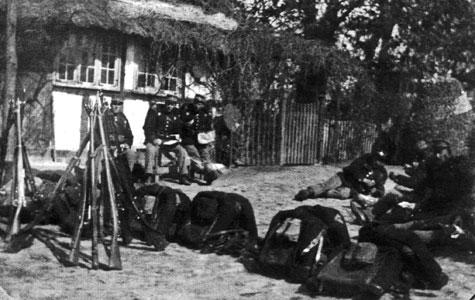 Indkvartering i Græse præstegård. Sognepræst C.W. Shiöpffe og kaptajn J. W. Jantzen, chef for andet kampagnnni, 18. bataillon. Soldater holder pause på gårdsplads, to gevær-pyramider ses, rygsækkene står i forgrunden.