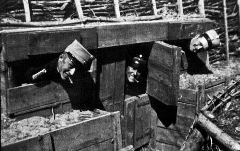 Tre soldater stikker hovederne ud af små glugger i en afstivet skyttegrav.