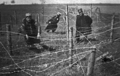 Her hænger tre soldater for sjov fast i rækker af pigtråd.