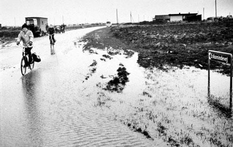 I de første år var der hverken anlagt asfalterede veje eller lavet kloaker. På fotografiet ses børn på vej i skole. Vejene og grundene er oversvømmet fordi sivebrøndene er oversvømmede.