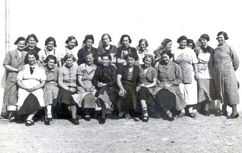 Kvindelige arbejdere på Gummifabrikken nyder solen i en pause. Billede fra ca. 1930.