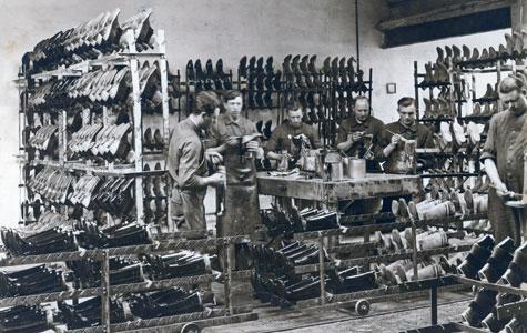 Mandlige arbejdere fremstiller gummistøvler og sko. Billedet er fra ca. 1930.