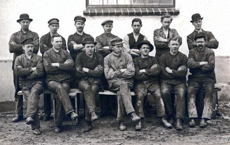 Ansatte på gummifabrikken. Hvad tænker du når du ser mændernes tøj og hatte? Billedet er taget omkring 1920.