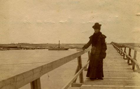 Her ses gangbroen fra 1905 fotograferet mens en elegant kvinde passerer.